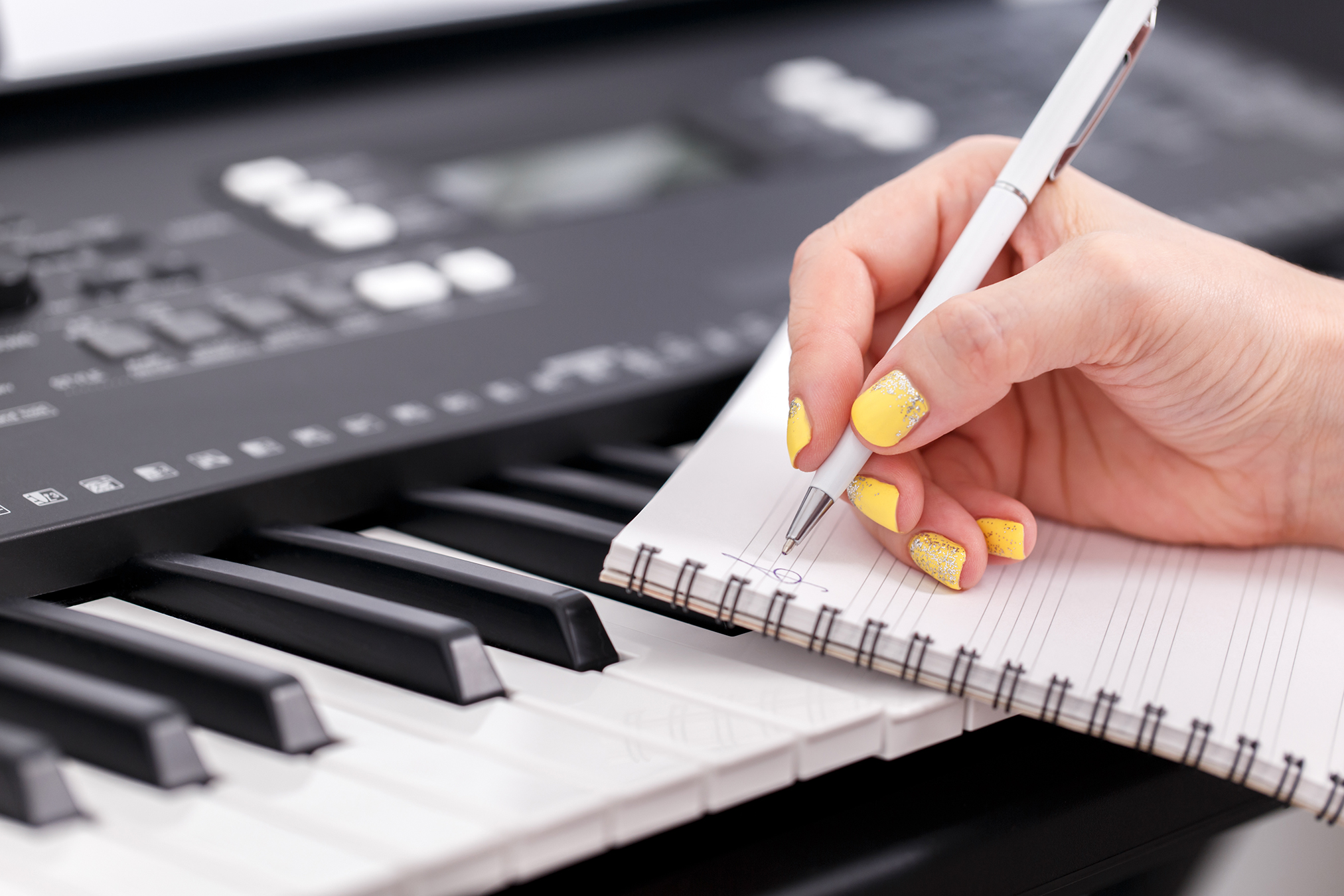 Woman writing music, close up of manicured hands on the electronic piano,